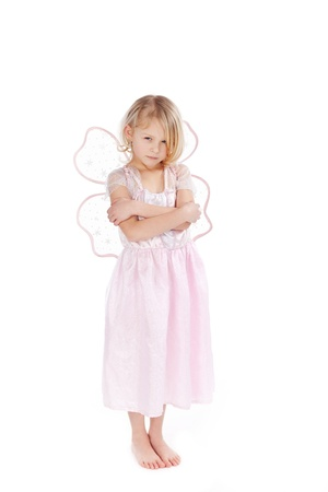 Angry little girl dressed as a pink fairy standing with crossed arms giving the camera a sulky look, isolated on white photo