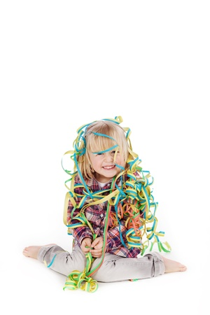 fringes: Full length portrait of little girl wrapped with ribbons while sitting isolated over white background Stock Photo
