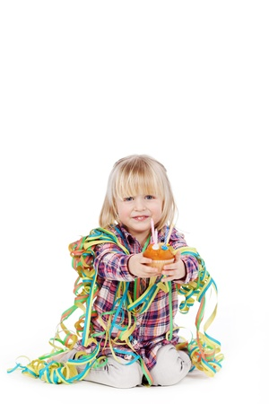 fringes: Portrait of little girl wrapped with ribbons offering cupcake isolated over white background