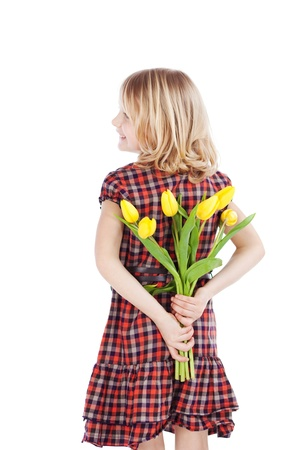 giving back: Young blond girl standing with a bunch of yellow tulips behind her back keeping them as a surprise for her mother on Mothers Day