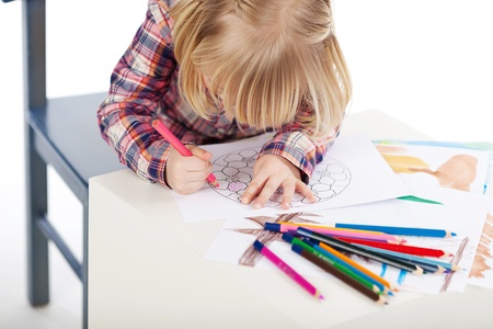 fringes: Little girl drawing at table isolated over white background