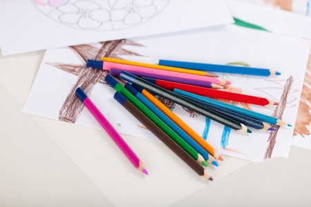 Colored pencils on drawing papers at table photo
