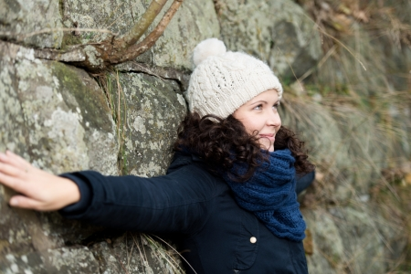 rock wool: Side view of beautiful young woman in winter clothes with arms outstretched leaning on stonewall