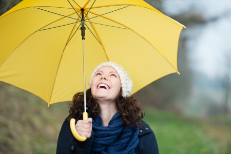 immune system: Happy young woman in winter clothes holding yellow umbrella in park