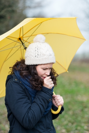Woman wrapped up warmly against the winter weather walking under an umbrella coughing from a seasonal cold and flu