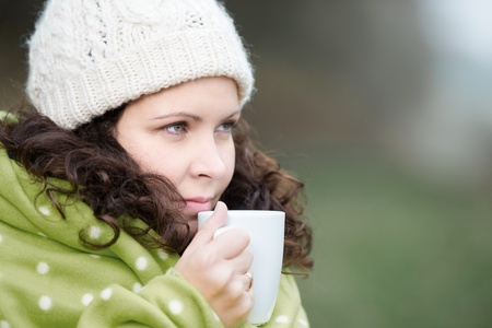 Closeup of young woman wrapped in scarf drinking coffee in park photo