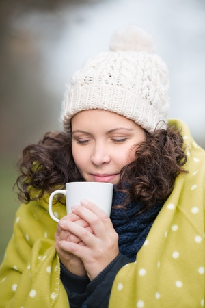 cradling: Woman enjoying a mug of tea in winter standing outdoors in the cold weather cradling the hot beverage in her hands while cuddling up in a blanket