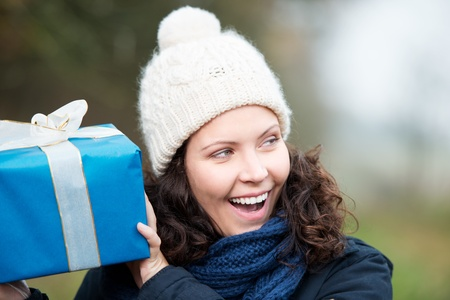 vivacious: Laughing vivacious woman in a winter cap shaking her gift and listening to see if she can identify the contents