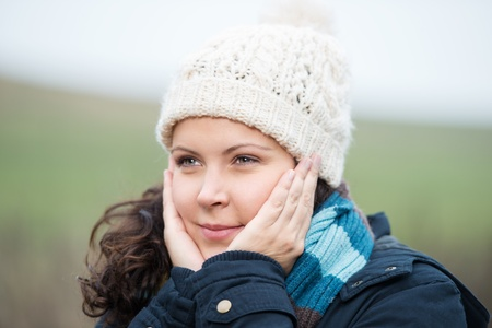 Woman outdoors in the cold winter weather warming her face with her hands photo