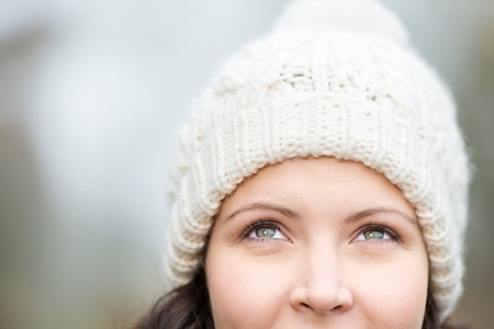 knit cap: Closeup of thoughtful young woman wearing knit hat while looking up