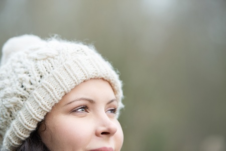 woolly: Smiling woman wearing a white knitted woolly cap in winter staring off into the distance lost in thought, with copyspace