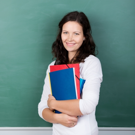 lecturer: Pretty woman student carrying her files clasped to her chest standing in front of the blackboard in the classroom with a lovely friendly smile