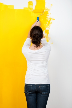 Rear view of woman using paintroller while painting wall at home photo