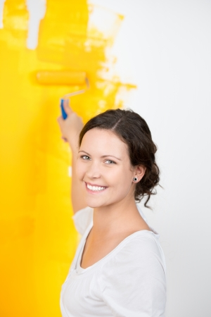 Portrait of happy young woman painting wall with paint roller photo