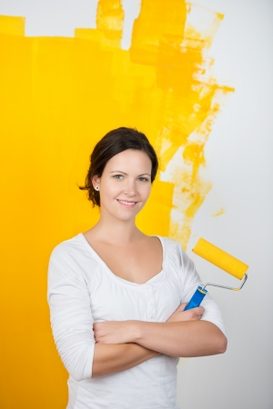 Confident young woman with a paint roller standing with her arms crossed in front of a half painted wall in her house done in bright yellow paint Stock Photo - 20736485