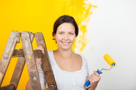 paintroller: Portrait of beautiful young woman with ladder holding paintroller against wall at home