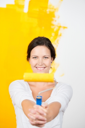 Smiling woman with a paint roller holding it out at arms length towards the camera as she pauses while painting a wall in her house bright yellow photo