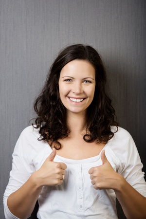 Portrait of confident young woman gesturing thumbs up against wall photo