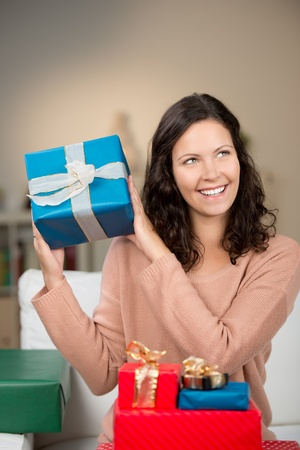 guessing: Happy beautiful young woman guessing the contents of her gifts holding a large blue one up in the air shaking it with a delightful smile Stock Photo