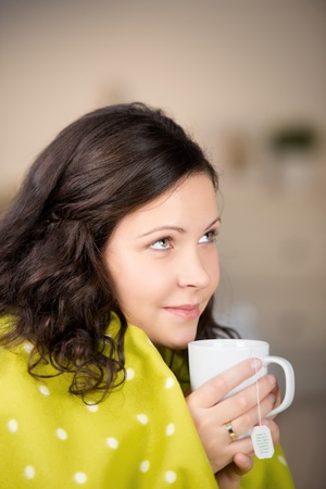 Woman warming herself with a large freshly brewed mug of tea sitting in a warm blanket smiling in appreciation photo