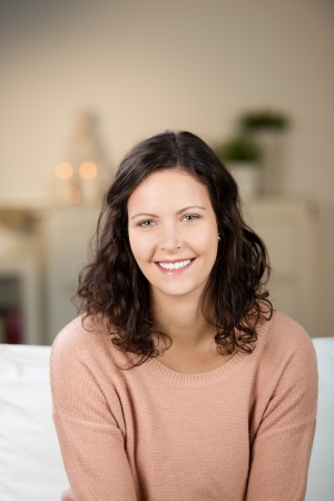 woman sweater: Portrait of pretty young woman smiling while sitting on sofa at home Stock Photo