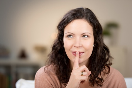 Closeup of young woman with finger on lips at home