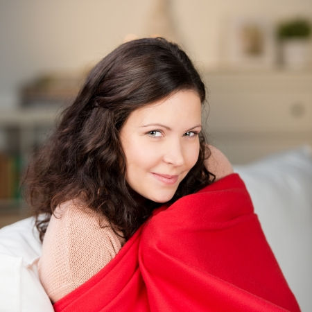 blanket: Portrait of young woman wrapped in shawl at home