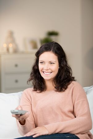 Smiling beautiful young woman watching television relaxing a a sofa with a remote control in her hand photo