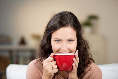 relaxes: Mujer que disfruta de una gran taza de t� caliente reci�n hecho mientras se relaja en un sof� en la sala de estar Foto de archivo