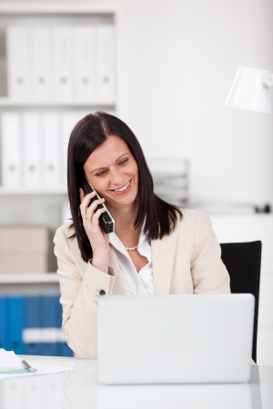 Smiling beautiful mature businesswoman sitting at her desk looking at her laptop screen while talking on the phone photo
