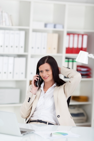 Successful businesswoman talking on the phone in her office sitting back in her chair at the desk in a relaxed position with her hand to her hair photo