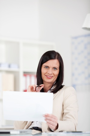 Businesswoman reading paperwork sitting at her desk with a blank white document in her hand photo