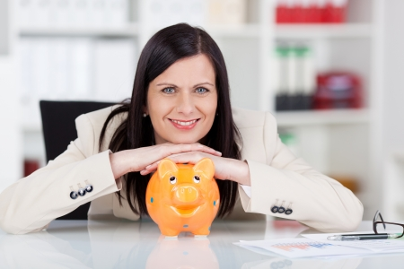 Successful smiling business woman with her piggy bank sitting at her desk in the office smiling at the camera with a beaming smile of satisfaction photo