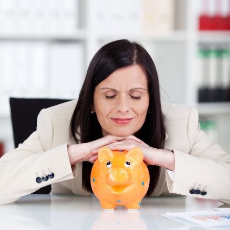 Businesswoman with a piggy bank resting her chin on the top with her eyes closed dreaming of riches and success photo
