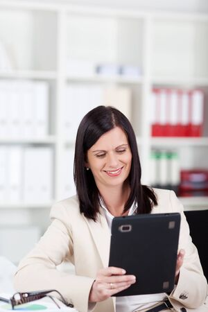 Businesswoman sitting in her office working with a tablet computer reading information on the screen with a pleased smile photo