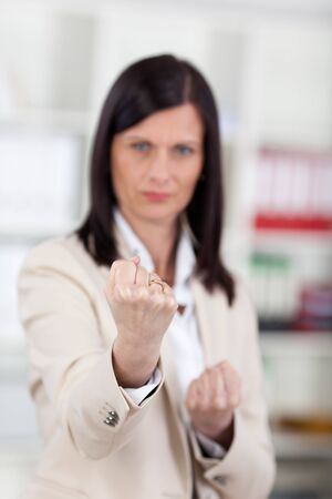 provocation: Businesswoman balling her fists at the camera with a determined expression, selective focus to the hands Stock Photo