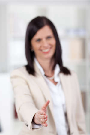 Businesswoman offering her hand in a business handshake to seal a business transaction or partnership, selective focus to her hand photo