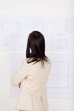 Confident successful female architect studying building blueprints pinned up on a board, rear view portrait in stylish jacket photo