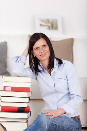 Beautiful casual woman sitting at home in her living room with a pile of hardcover books leaning her elbow on the top of the stack and smiling at the camera photo