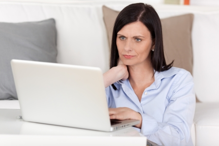 Closeup portrait fof a beautiful serious woman working on a laptop at home reading information on the screen