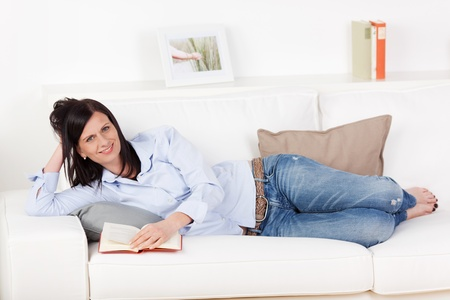 recline: Smiling attractive young woman lying stretched out reading on a sofa in jeans and bare feet Stock Photo
