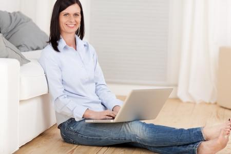 Atractiva joven sentado en el suelo en su sala de estar apoyada en un sofá con un ordenador portátil en equilibrio sobre su regazo