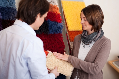 carpet color: Couple choosing a carpet holding up a sample swatch in her hands while discussing it with a decorator or salesman Stock Photo