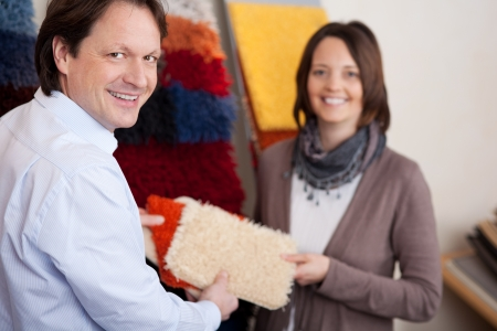 Man and woman holding choosing a new carpet Stock Photo - 20772061