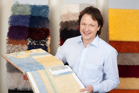 floor coverings: Friendly salesman with fabric and carpet samples in a book in his hands loking at the camera with a smile