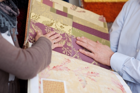 Woman looking at wallpaper and fabric swatches holding a sample book in her hands while discussing them with a male partner or salesman