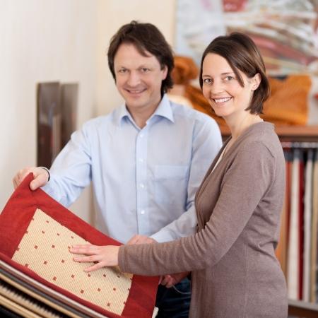 vergezeld: Vrouw op zoek naar tapijt monsters staan kijken naar een monster boek vergezeld van een lachende jonge man of verkoper