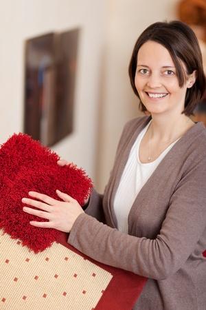 decide: Mujer sonriente con muestras de la alfombra se muestran en sus manos en tonos de rojo mientras se decide sobre las telas de su nueva casa