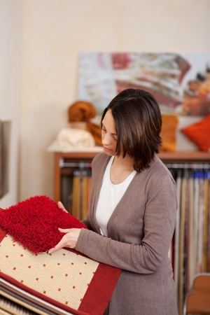 Woman looking at red carpet samples deciding on the colour and texture best suited to her new house interior photo