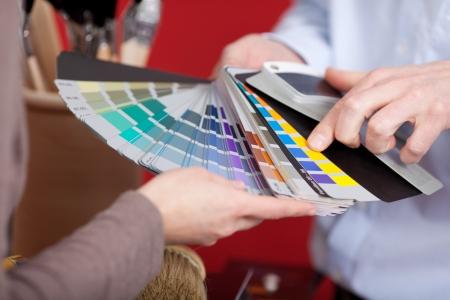 Decoratore d'interni in un incontro con un cliente che parlano di vari colori di vernice da un insieme variopinto di campioni che sta tenendo in mano Archivio Fotografico - 20849786
